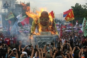 <span>Protesters burn the effigy of President Benigno Aquino lll along Commonwealth Avenue, Quezon City during his last State of the Nation Address. </span>
